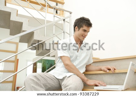 Professional young man using a laptop computer while sitting down on a modern stairwell.