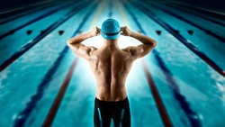 Professional young muscular swimmer jumping from starting block in a swimming pool