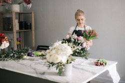 Professional young woman florist wearing apron making floral arrangement from fresh tulip at the table on white background. Concept of working with flowers, floral business.