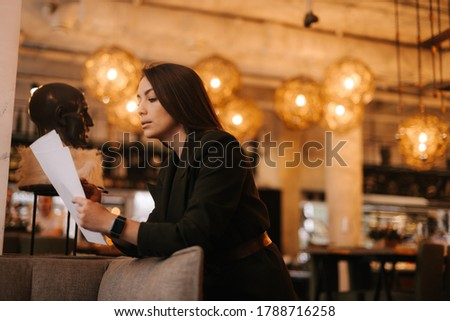 Professional young woman inspector wearing stylish formal clothes in modern luxury restaurant writing in paper documents with pen. Business lady lady in suit posing in cafe. stock photo
