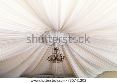 Professionally decorated with ceiling draping with sparkling chandelier in the centre for any occasion or special event. With copy space.
