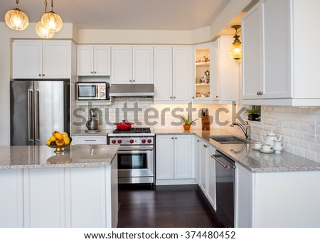 Professionally designed new kitchen with touch of retro. Professional gas range and hood, white cabinet,  antique ceiling lamp, fine bone china teacups in cabinets. Interior design ideas.