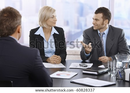 Professionals discussing work sitting in meeting room.