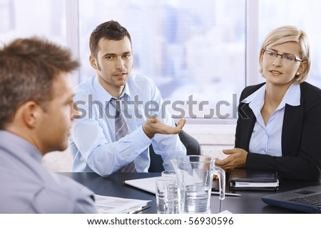 Professionals sitting at meeting table, discussing work problems in skyscraper office.?