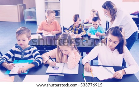 Professor and elementary age children at the classroom in a school