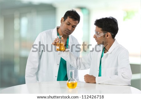 Professor and student or Scientific researchers looking at a liquid solution.