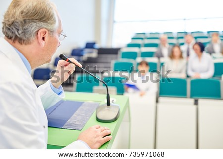 Professor giving medicine lecture to doctors for training in lecture hall