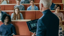 Professor of Computer Science Reads Lecture to a Classroom Full of Multi Ethnic Students. Teacher Holds Laptop with Deep Learning, Artificial Intelligence Infographics on the Screen.