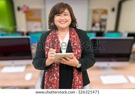 Professor Senior woman using the tablet on the Abstract blurred photo of empty server room, education and business concept