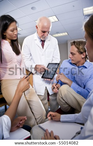 Professor wearing lab coat having discussion with college students