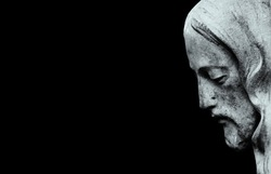 Profil of Jesus Christ isolated on black background. (ancient statue)