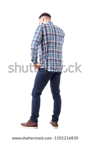 Profile back view of caucasian business man talking on the phone looking down with hand on hip. Full body isolated on white background.