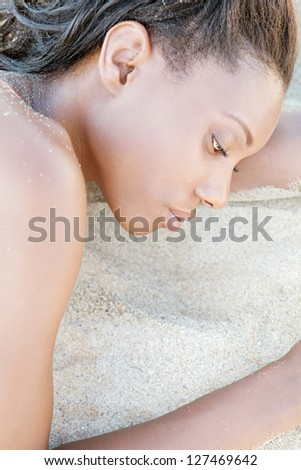 Profile close up beauty portrait of an attractive black woman with perfect skin, laying down on a white sand beach, relaxing.