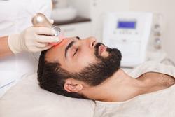 Profile close up of a bearded man enjoying rf-lifting treatment at beauty clinic