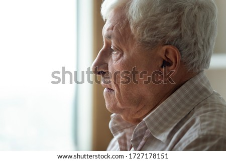 Profile close up view of sad lonely elderly man look in distance pondering or thinking, upset distressed senior grandfather feel loneliness and solitude, mourn or yearn at home or retirement house