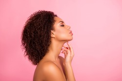 Profile, half face portrait of naked sensual, confident, attractive, brunette, charming, pretty enjoying her perfect skin with close eyes, touching her neck with fingers, isolated on pink background