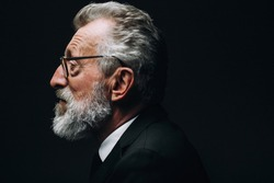 Profile headshot of intelligent bearded grey haired scientist listening report, dressed in formal black suit, sitting isolated over dark