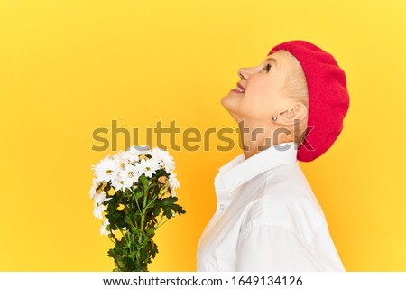 Photo of Profile image of stylish mature blonde lady in red bonnet being in good mood smiling broadly with excitement, feeling happy and free, receiving cute bouquet of white dandelion flowers on birthday