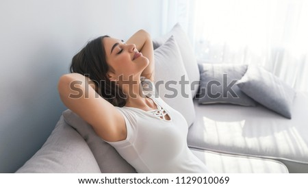 Profile of a beautiful woman relaxing lying on a couch at home. Portrait of a girl relaxing on a sofa after work at home sitting on a sofa in the living room at home #1129010069