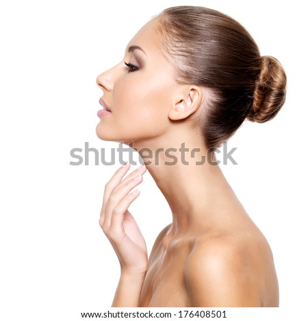 Profile of a beautiful young woman with fresh clean skin gently touching her neck isolated on white