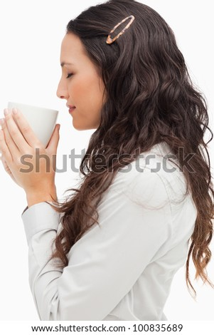 Profile of a brunette smelling a hot coffee against white background