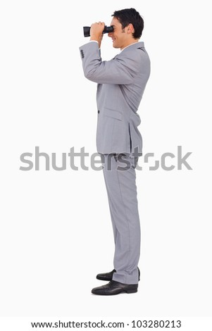 Profile of a businessman using binoculars against white background