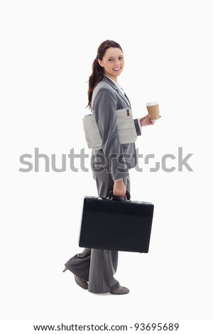 Profile of a businesswoman smiling, walking with a briefcase, with a newspaper under her arm and holding coffee against white background