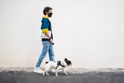 Profile of a full-length young man walking with his French bulldog (canis lupus familiaris) pet wearing a safety mask against coronavirus. People walking with dogs in a quarantine lockdown concept.