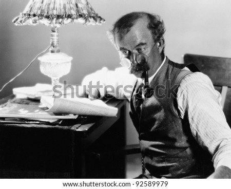 Profile of a man sitting at a desk and holding a book and smoking a pipe