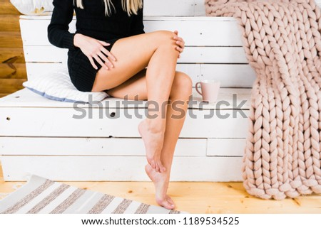 Profile of a perfect woman legs sitting on a couch at home. Attractive model posing and caresses his legs. Concept of a hair removal and health care. Close up