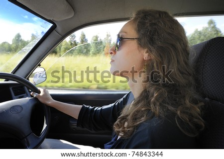 profile of a pretty young woman in sunglasses driving a right-hand drive vehicle