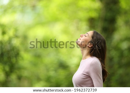 Profile of a relaxed woman breathing fresh air in a green forest
