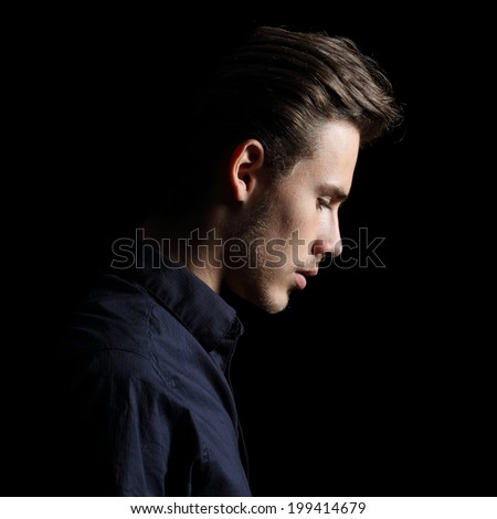 Profile of a sad man face crestfallen on black isolated on a black background
