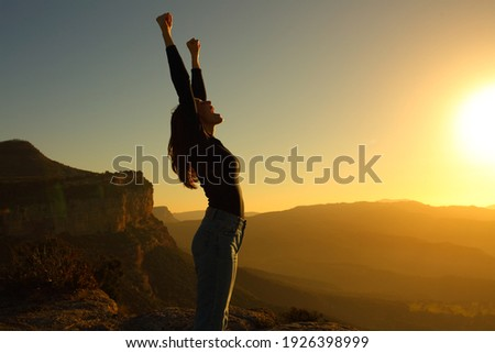 Profile of a silhouette of a woman screaming raising arms celebrating vacation at sunset in the mountain Foto stock ©