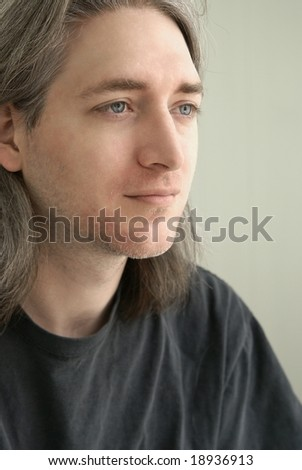 Profile of a thirty something year old man with long salt and pepper hair.