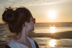 Profile of a woman silhouette watching sun on the beach at sunset