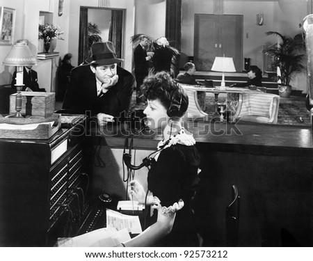 Profile of a woman working on the telephone switchboard with a man looking at her