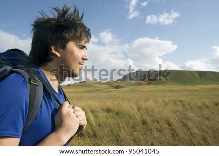 Profile of a young backpacker with green valley in the background