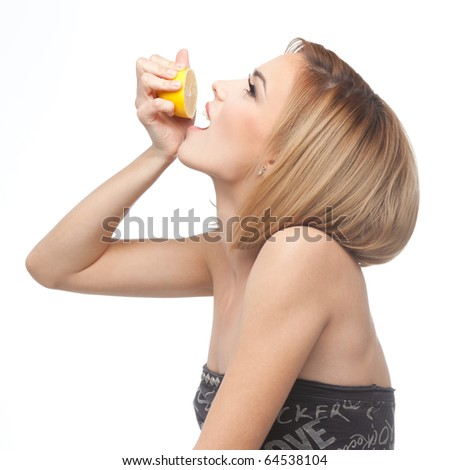 profile of a young, blonde woman, pouring lemon juice in her mouth, from a slice of lemon she squeezes in her hand.