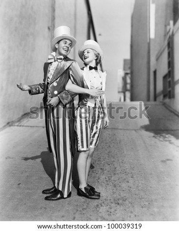 Profile of a young man and a young woman standing with arm in arm in a costume
