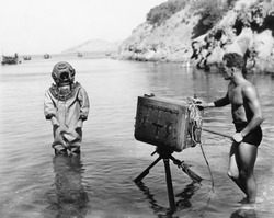 Profile of a young man holding a camera with a scuba diver standing in front of him on the beach