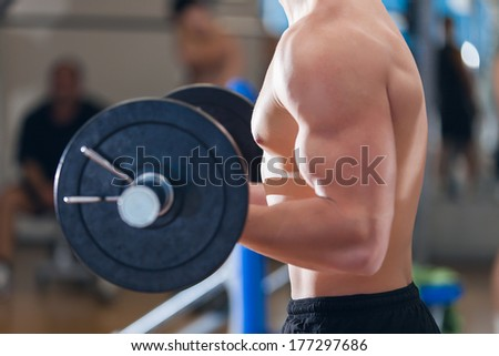 Profile of a young man working out in the gym