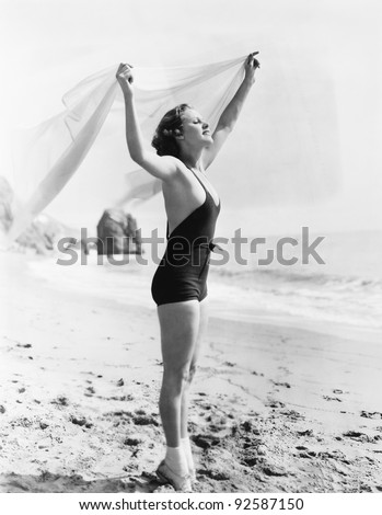 Profile of a young woman holding up a sarong at the beach