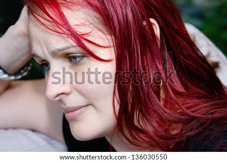 profile of a young woman in an anxious state, deep in thought looking worried