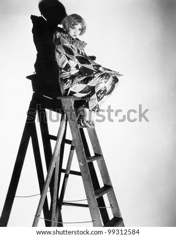 Profile of a young woman sitting on a ladder