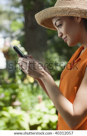 Profile of a young woman standing in a garden and looking at her cell phone. Vertical format. - stock photo