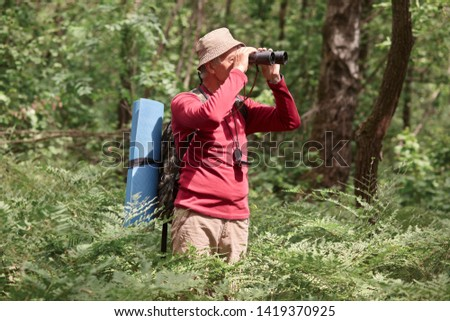 Profile of active hicker looking through binoculars, having compass on his neck, wearing sweatshirt and trousers, taking backbacker and and sleeping pad with him, going camping. Activities concept. #1419370925