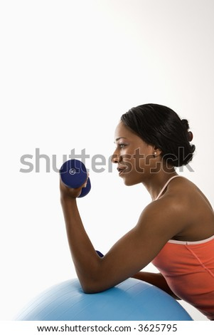 Profile of African American young adult woman leaning on exercise ball holding dumbbell.