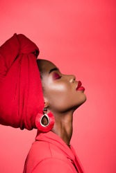 profile of african american young woman in stylish outfit and turban with closed eyes isolated on red