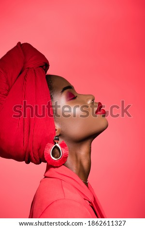 profile of african american young woman in stylish outfit and turban with closed eyes isolated on red Stockfoto ©